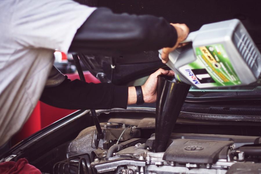 personne qui change l'huile de moteur