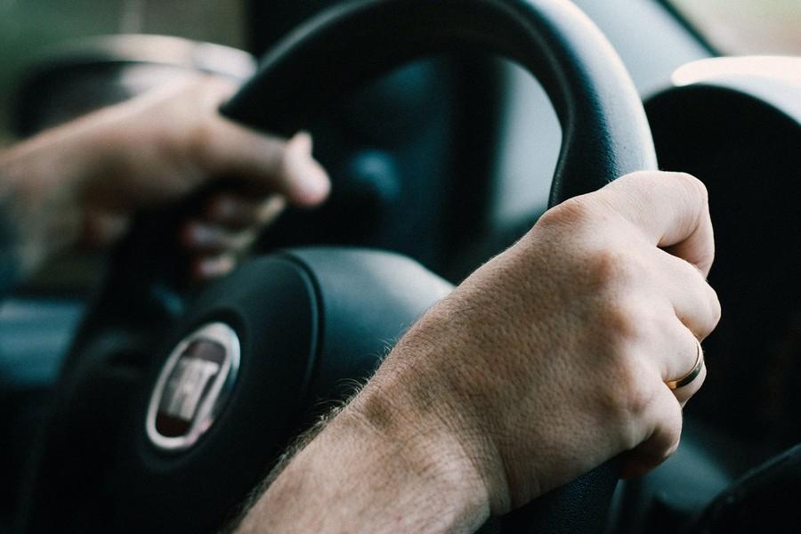 mains posées sur un volant de voiture